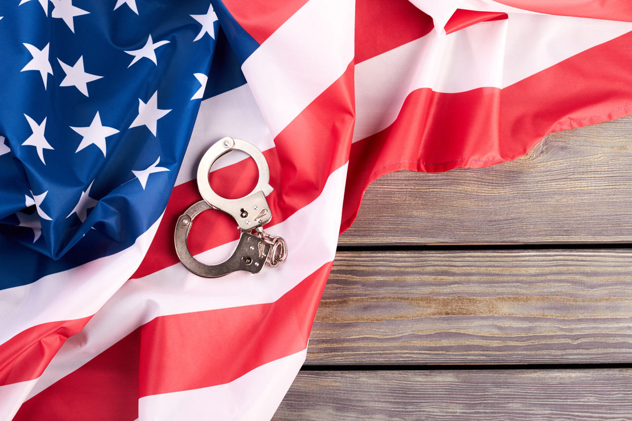 USA flag and handcuffs, top view.